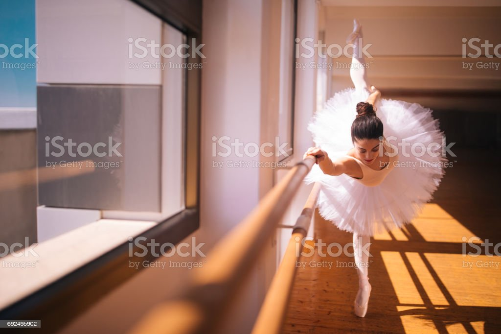 Ballerina on her tiptoes with one leg in the air stock photo