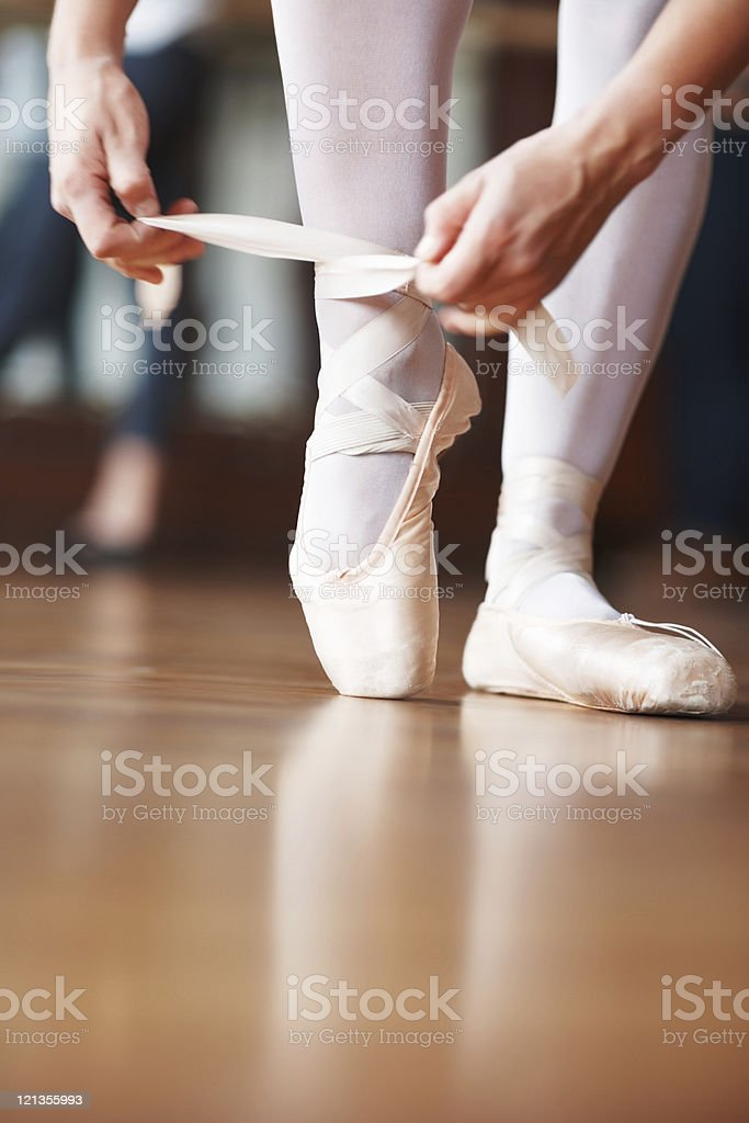 Ballerina putting her shoes stock photo