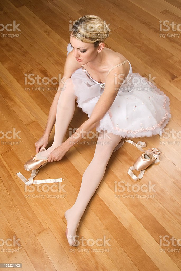 Ballerina putting on her ballet shoes royalty-free stock photo