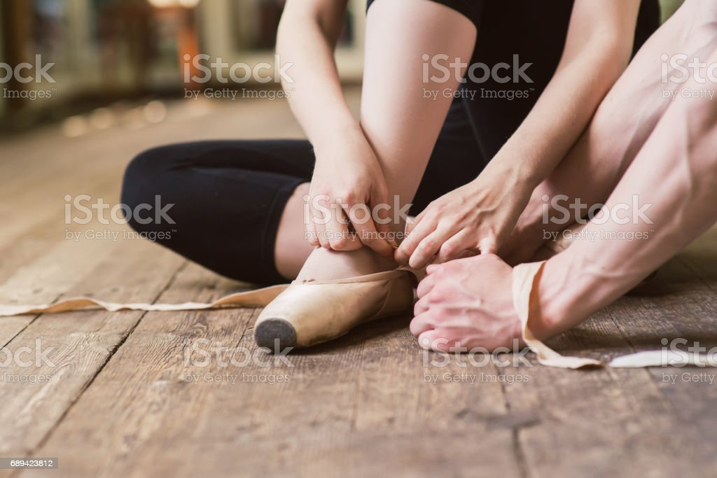 Ballerina putting on her ballet shoes stock photo