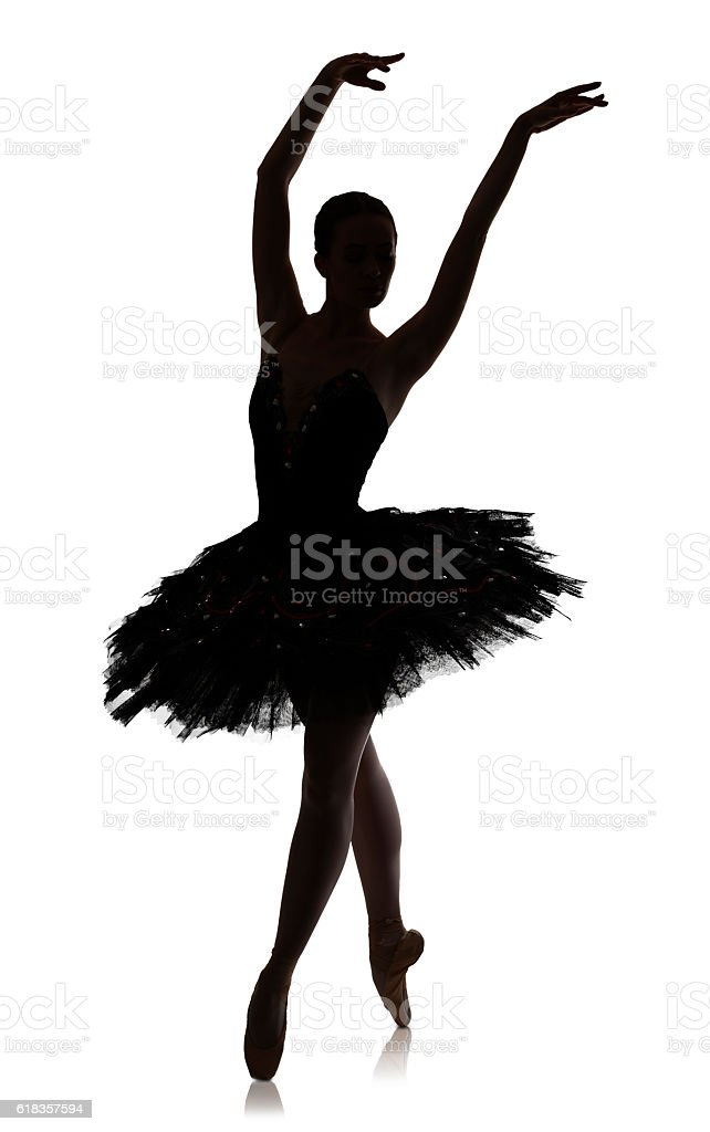 Ballerina silhouette making ballet position pirouette against white background, isolated stock photo