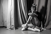 Ballerina sitting on the stage. black and white photo