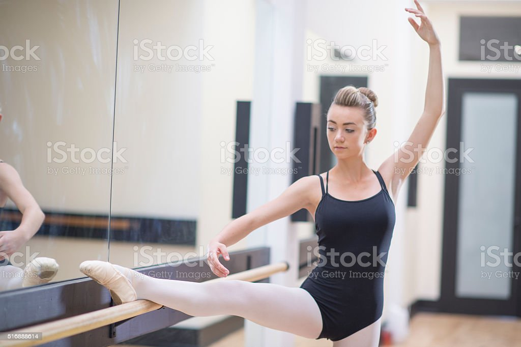 Ballerina Stretching on a Barre stock photo
