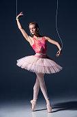 ballet dancer as puppet dancing over gray background