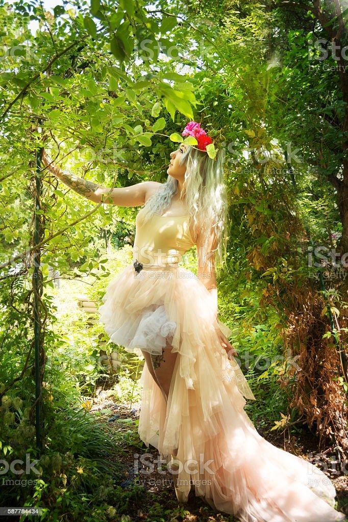 Ballet dancer in garden, side view standing in arch. stock photo