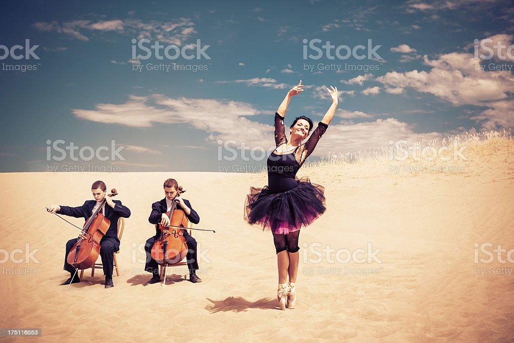 Ballet Dancer Poses En Pointe And Cellist In The Desert stock photo