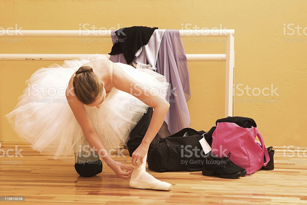 Ballet dancer preparing to practice on pointe shoes royalty-free stock photo