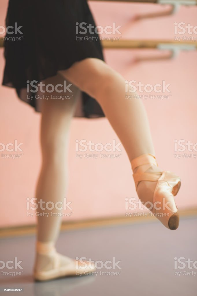 Ballet dancer stretching next to a barre stock photo
