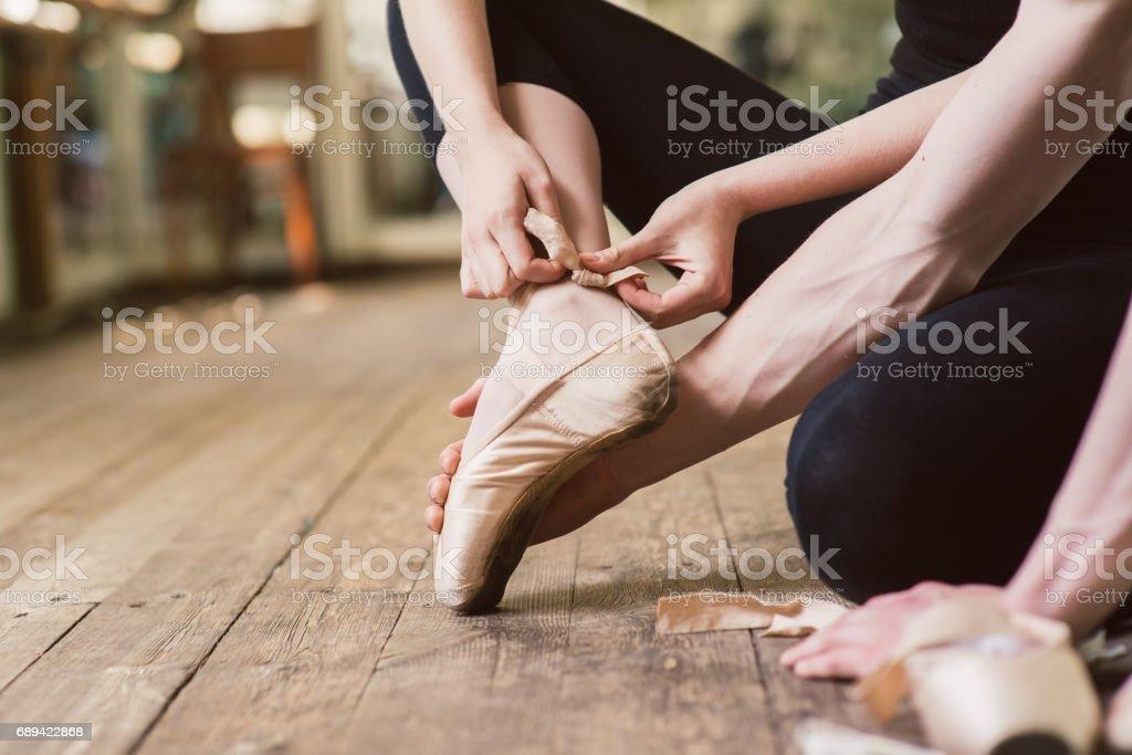 Ballet dancer tying ballet shoes stock photo