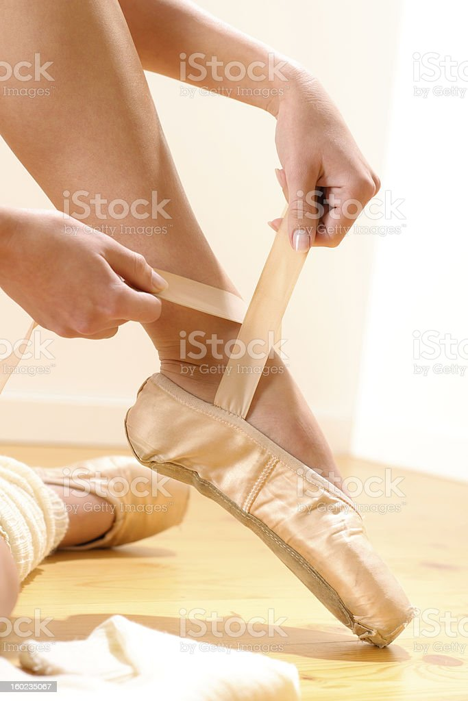 Ballet dancer tying slippers around her ankle royalty-free stock photo