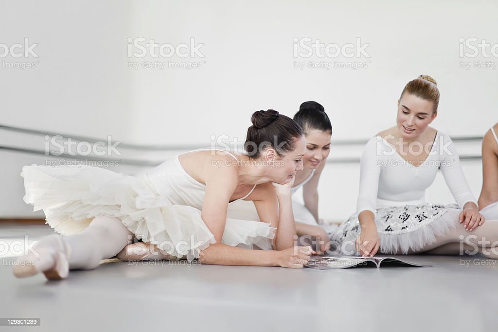 Ballet dancers reading magazine together royalty-free stock photo
