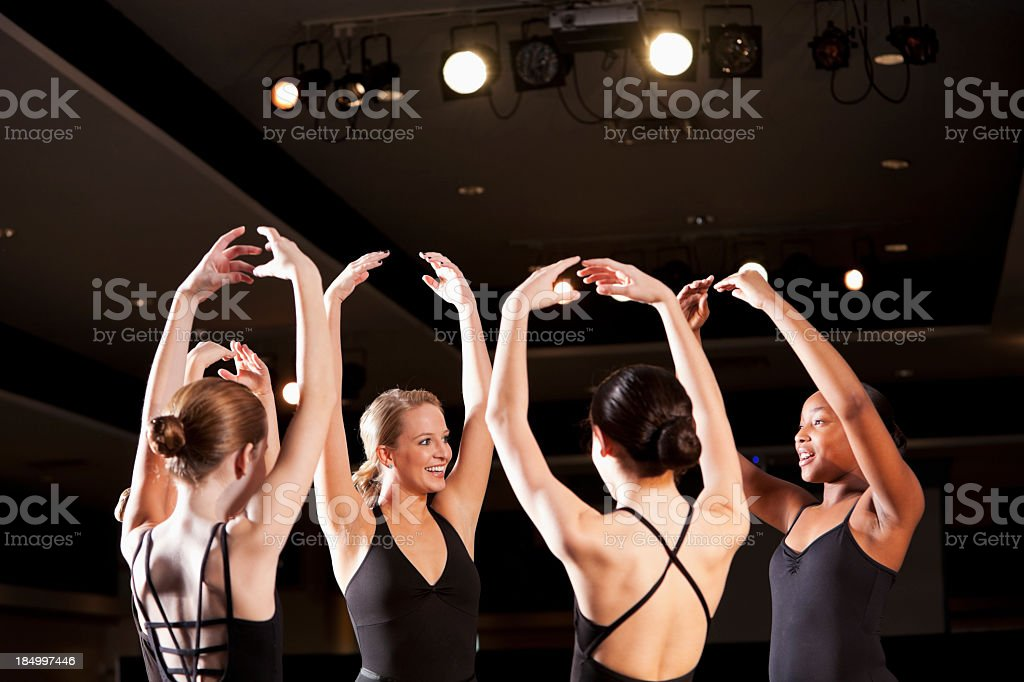 Ballet instructor with students on stage in auditorium royalty-free stock photo