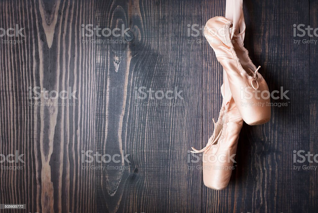 Ballet shoes on a wooden background stock photo