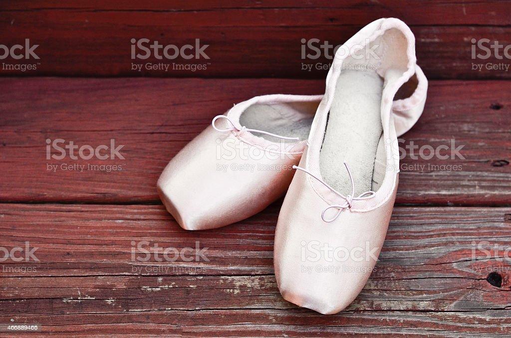Ballet shoes on wooden floor stock photo