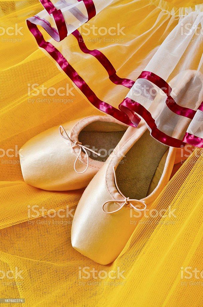 Ballet shoes on yellow tutu background stock photo