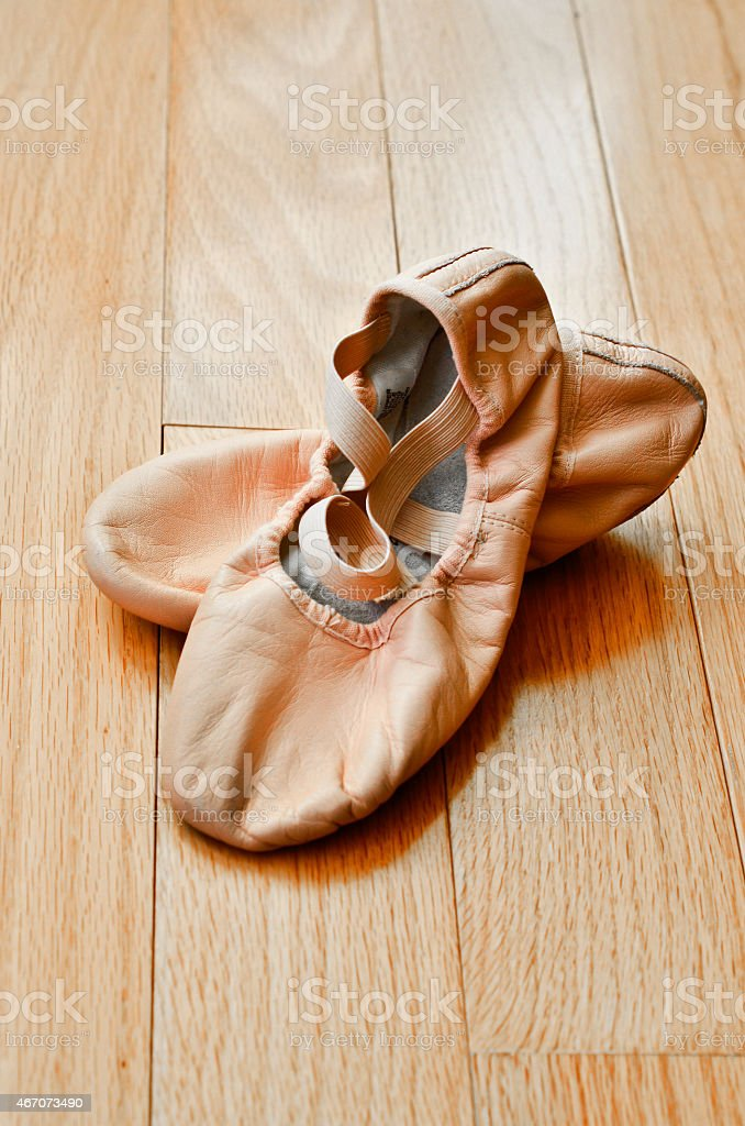 Ballet slippers on wooden floor stock photo