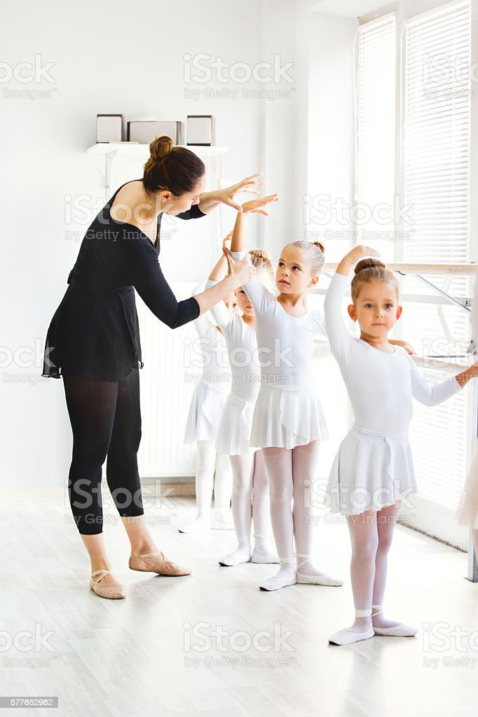 Ballet teacher helping girls with postures during ballet class. stock photo