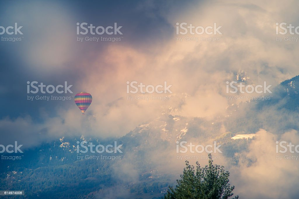 balloon among snowy mountains and clouds stock photo