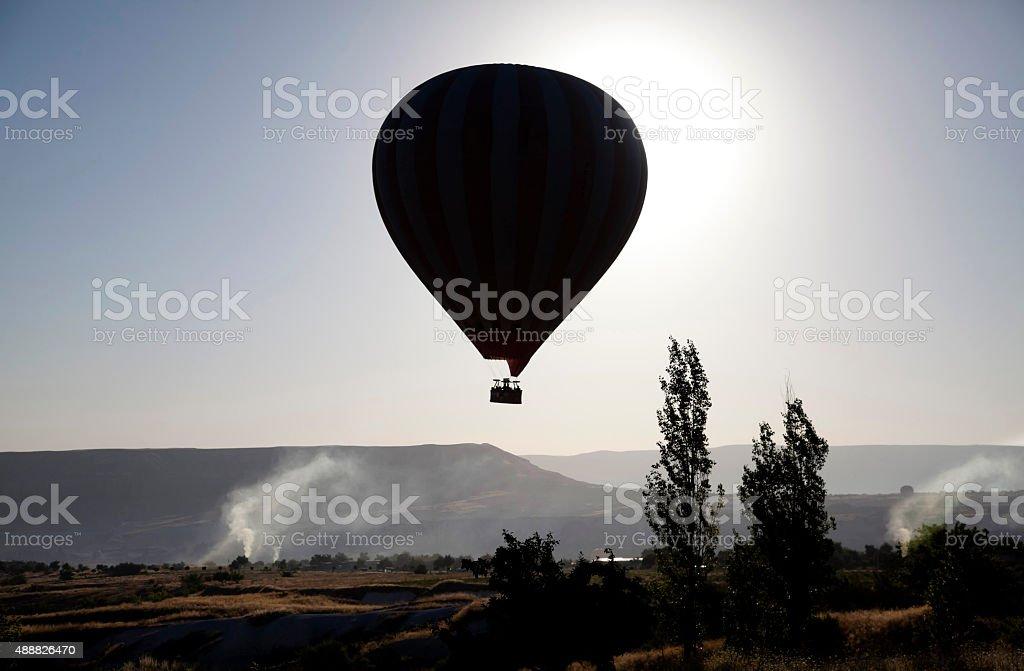 Balloon over the volcanic mountain landscape of Cappadocia stock photo