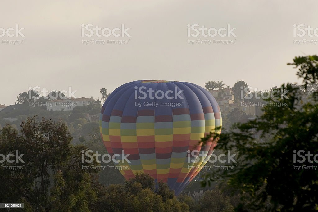 Balloon taking off over homes. royalty-free stock photo