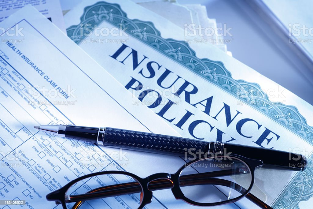 Ballpoint pen and eyeglasses on insurance policy and claim form stock photo