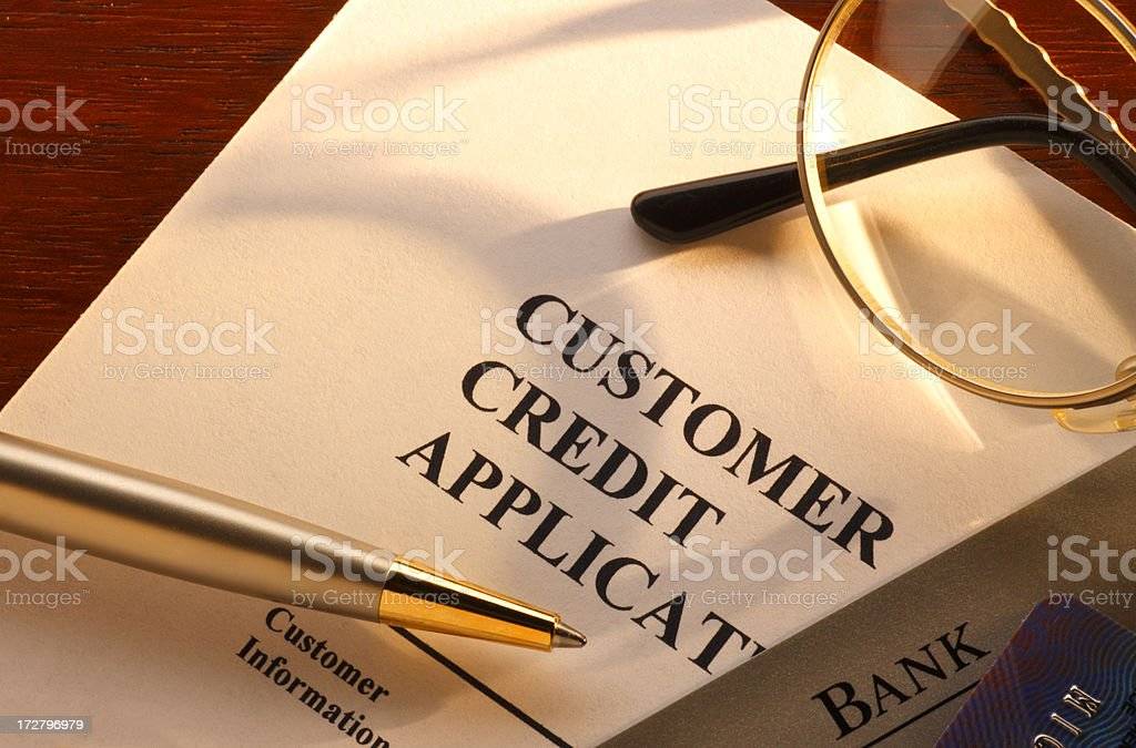 Ballpoint pen and eyeglasses on top of customer credit application stock photo
