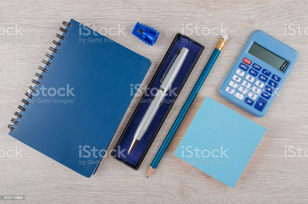 Ballpoint pen in box, pencil, notepad and calculator stock photo