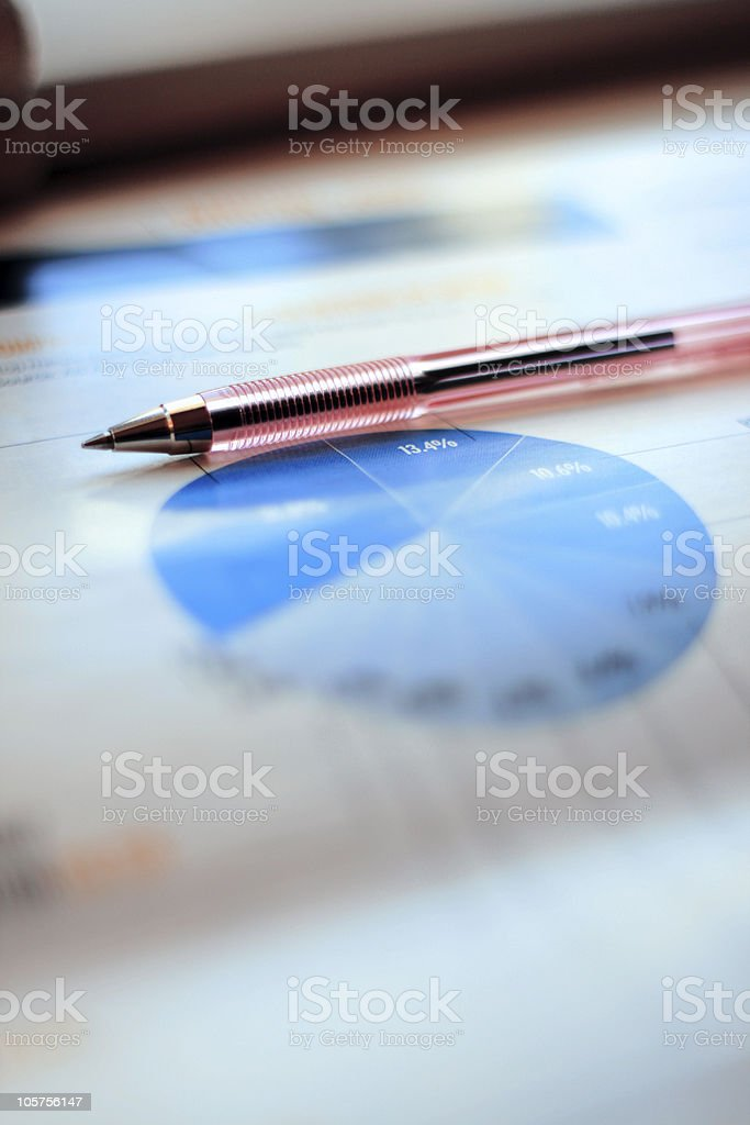 Ball-Point Pen Lying on a Financial Pie Chart stock photo