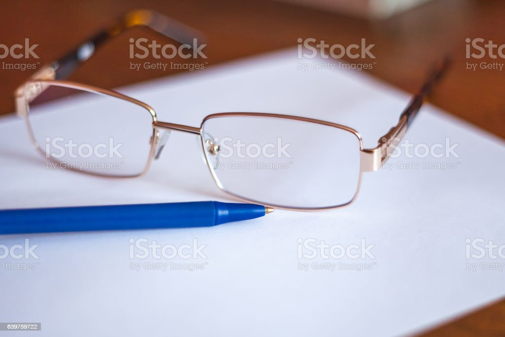 ballpoint pen on a sheet and reading glasses stock photo