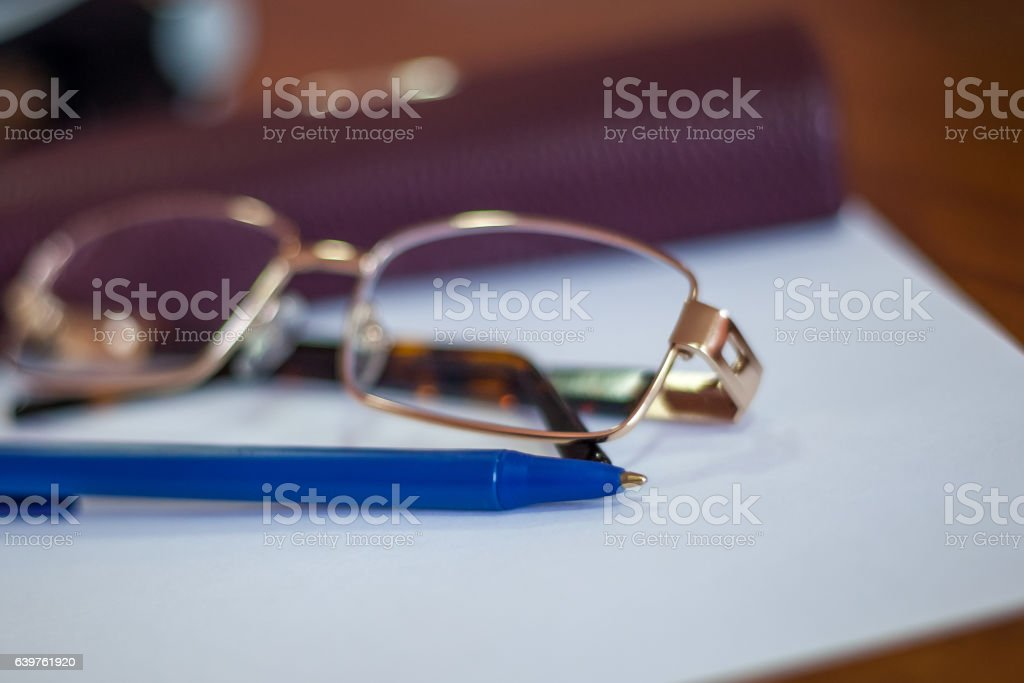 ballpoint pen on a sheet and reading glasses with box stock photo