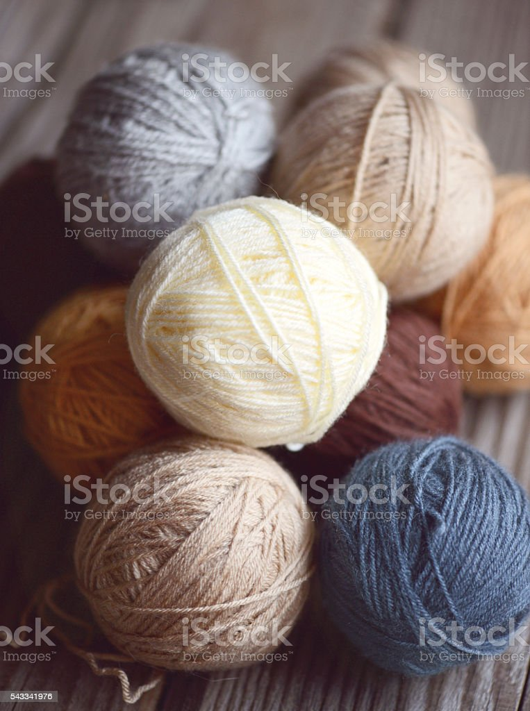 balls of wool on a wooden background stock photo