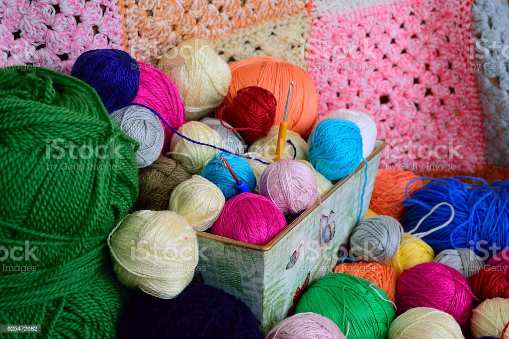 Balls of yarn in a basket with colorful crochet background stock photo