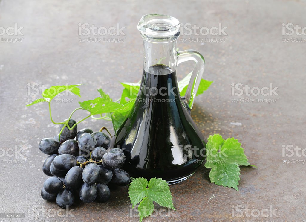 balsamic vinegar in a glass jug with fresh grapes stock photo