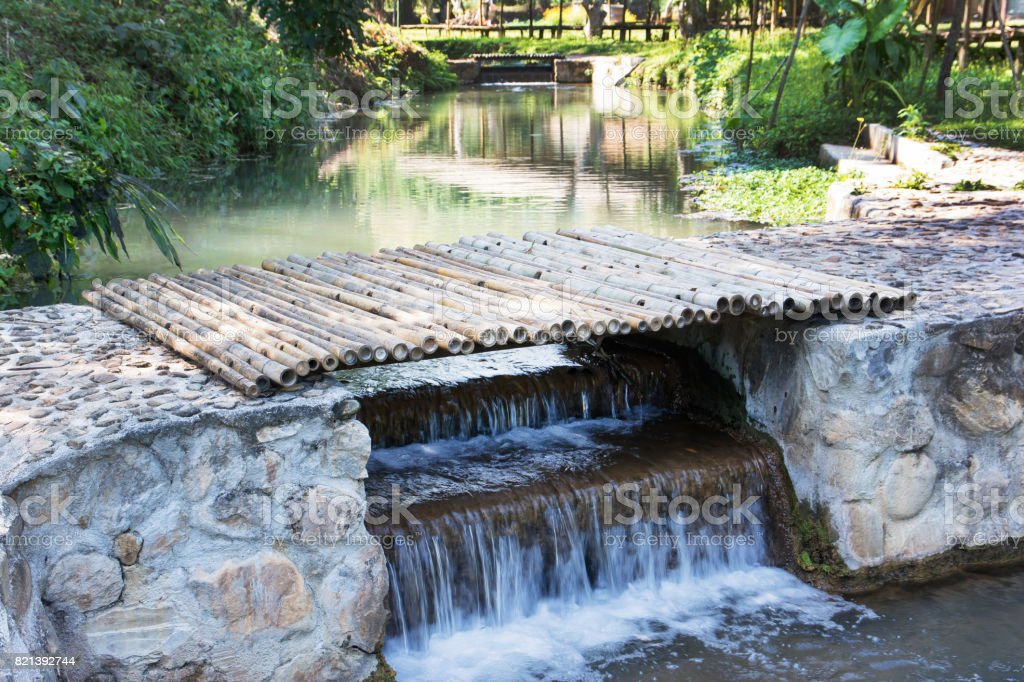 Bamboo bridge over small weir background.Wooden bridge with stream weir stock photo