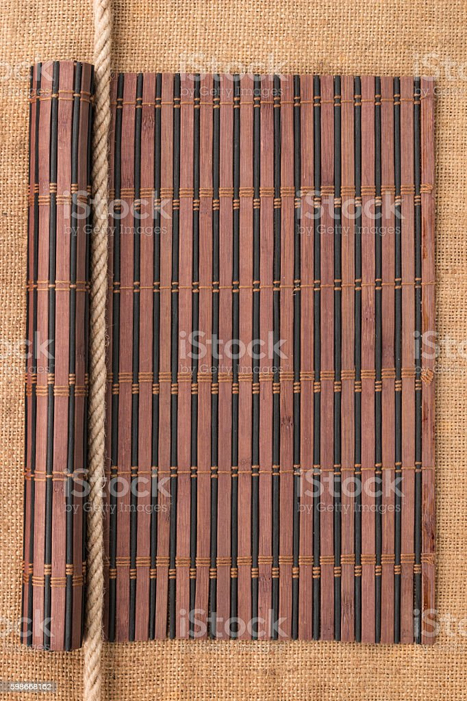 Bamboo mat rolled into a scroll and rope, lying on stock photo