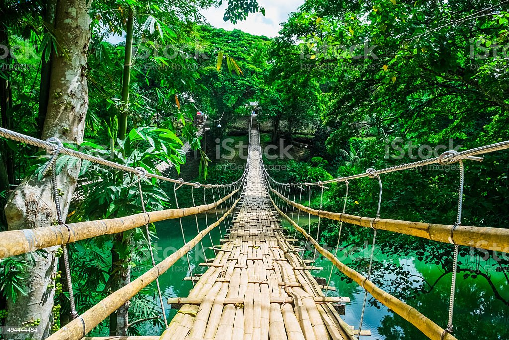 Bamboo pedestrian suspension bridge over river stock photo