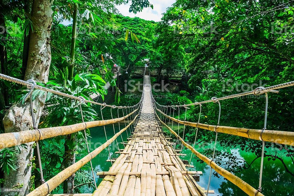 Bamboo pedestrian suspension bridge over river stock photo