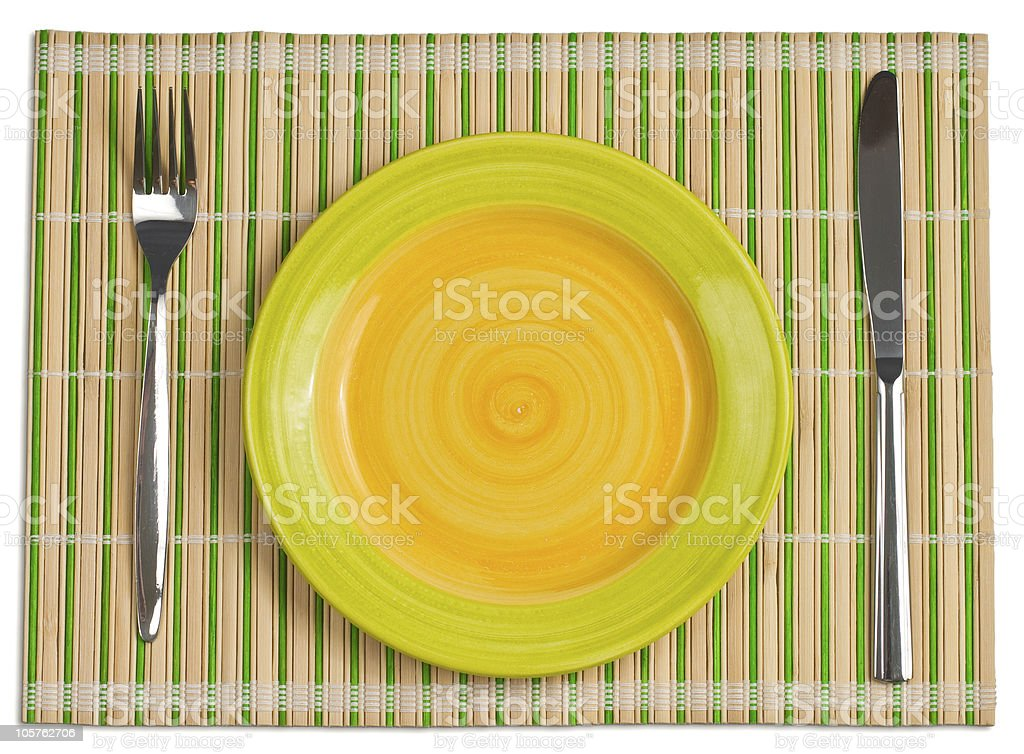 Bamboo placemat with plate fork and knife isolated on white royalty-free stock photo