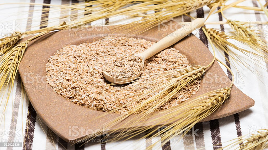Bamboo plate and wooden spoon filled with wheat bran stock photo