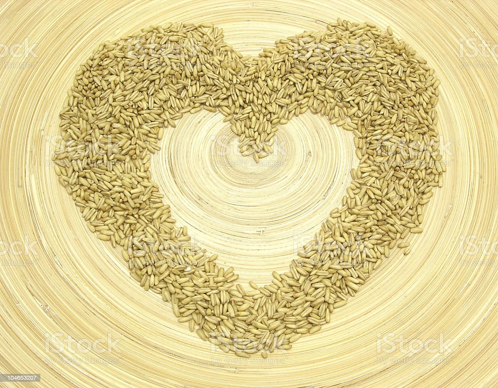 Bamboo plate with heart out of grain stock photo