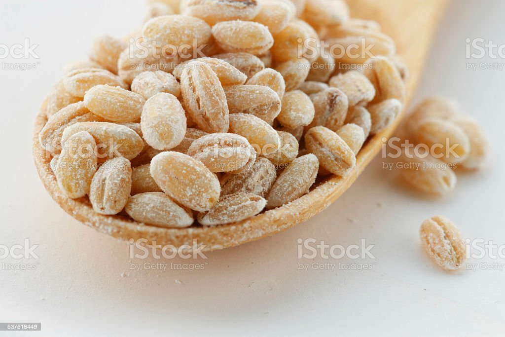 Bamboo spoon with pearl barley closeup stock photo