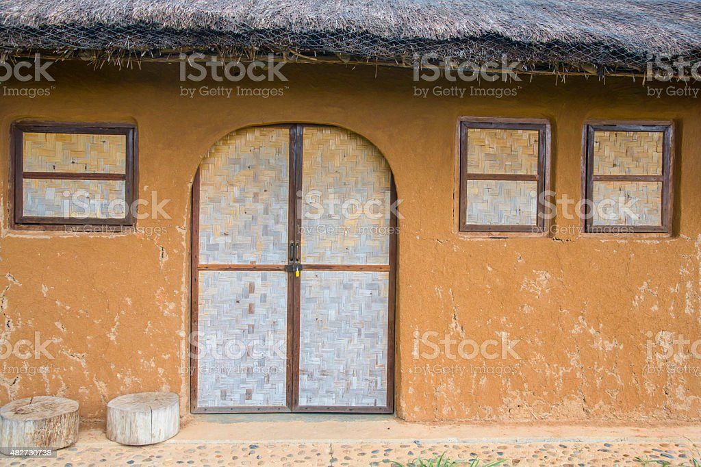 Bamboo wickerwork window of a vintage cob house stock photo