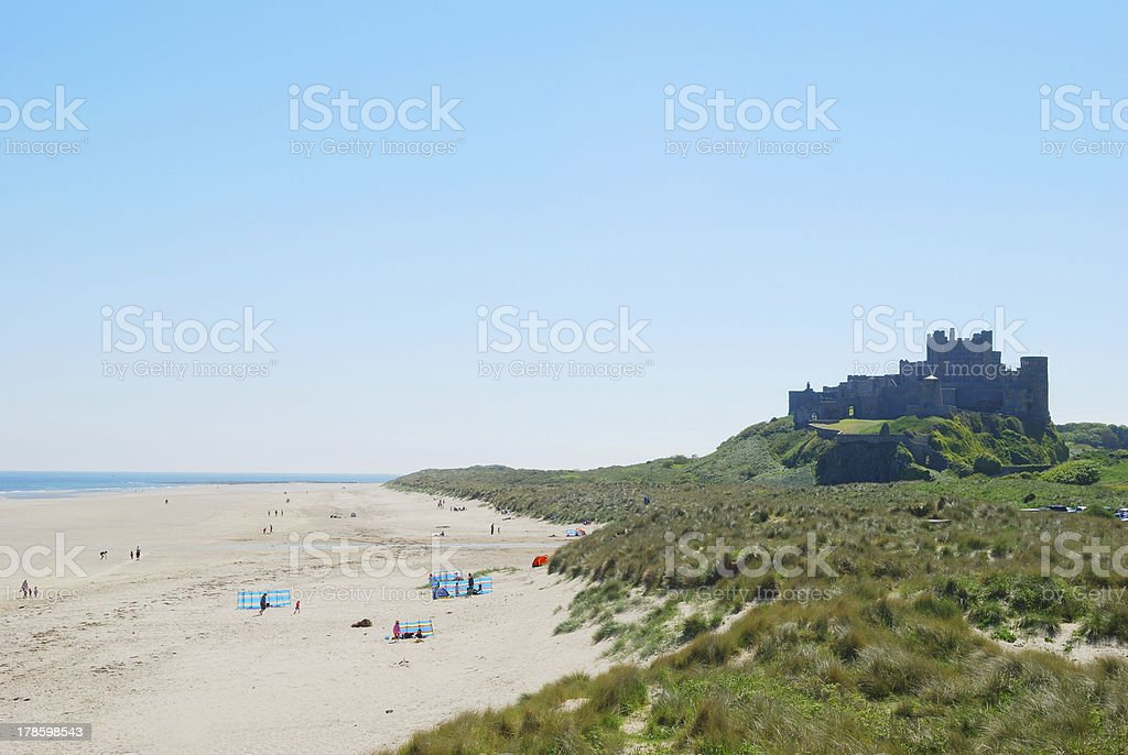 Bamburgh castle and beach on hazy summer day royalty-free stock photo