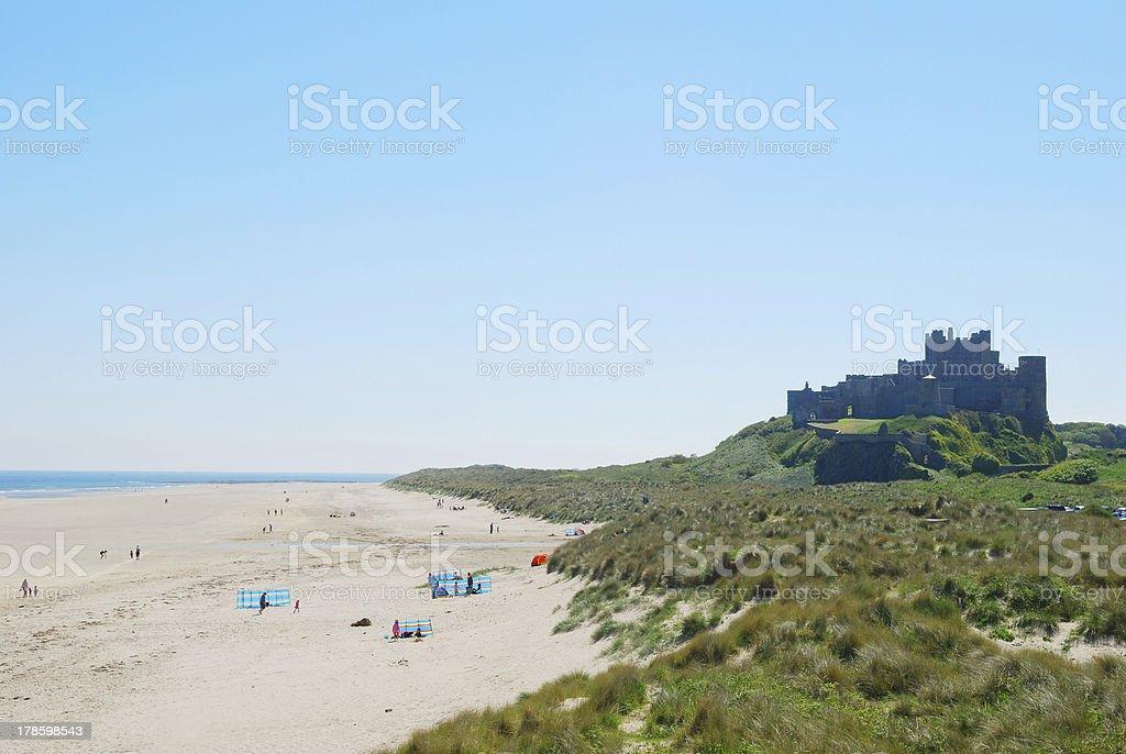 Bamburgh castle and beach on hazy summer day stock photo