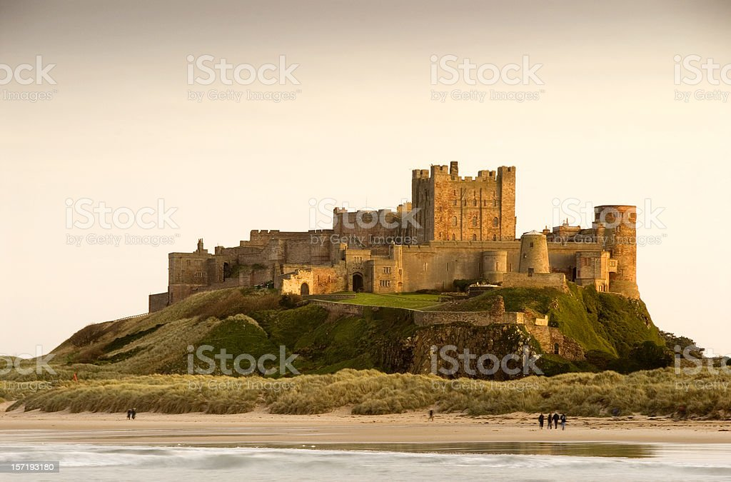 Bamburgh Castle daytime with people walking on beach stock photo