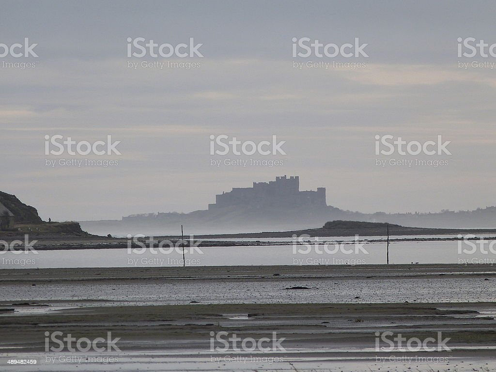 Bamburgh Castle silhouette from the beach stock photo
