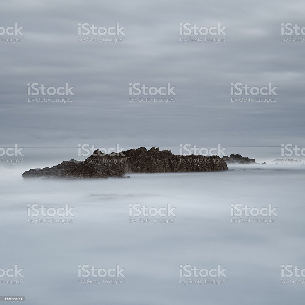 Bamburgh rocks in long exposure royalty-free stock photo