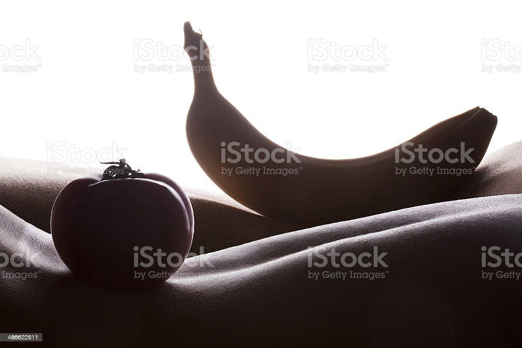 Banana and tomato on woman skin stock photo