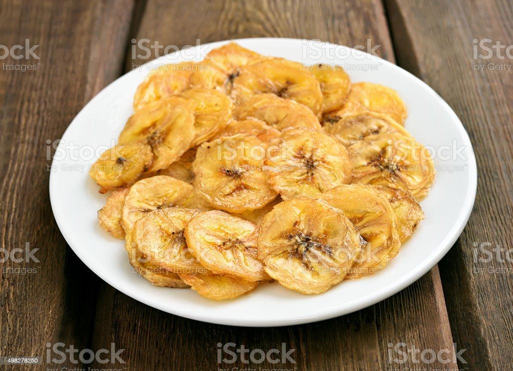 Banana chips on white plate stock photo