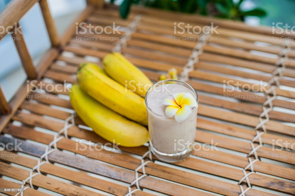Banana cocktail and fresh bananas on a bamboo table stock photo